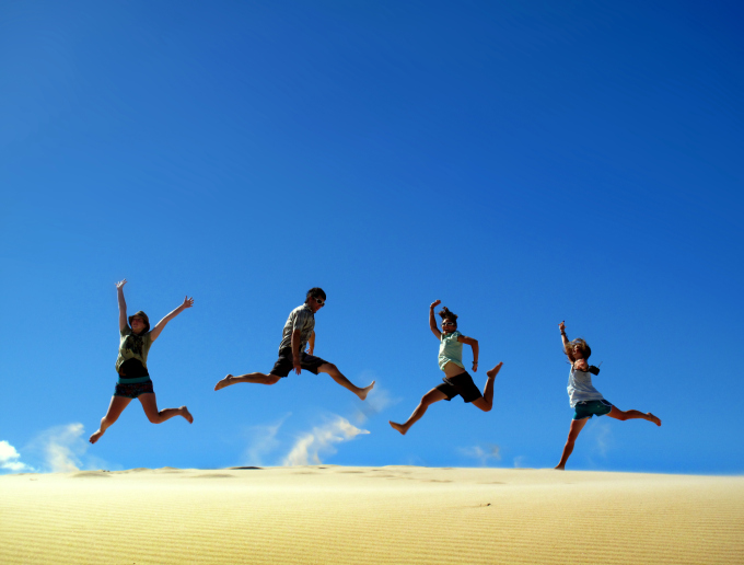 People jumping on sand dune
